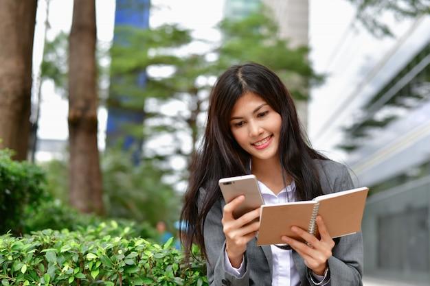Conceptos de comunicación empresarial. joven empresaria feliz de jugar móvil.