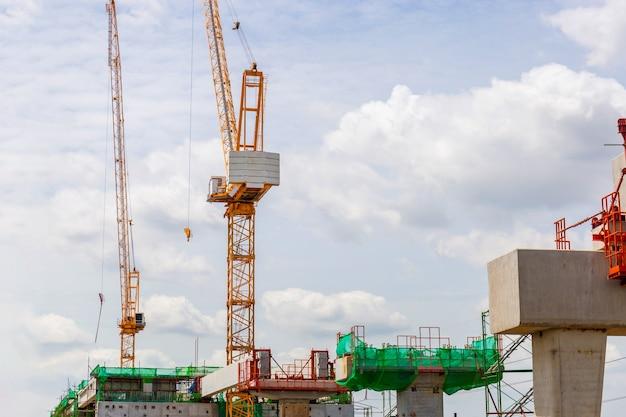 Conceptos de construcción de infraestructura, construcción de una línea de tren de tránsito masivo en progreso con grúas de construcción e infraestructura pesada.