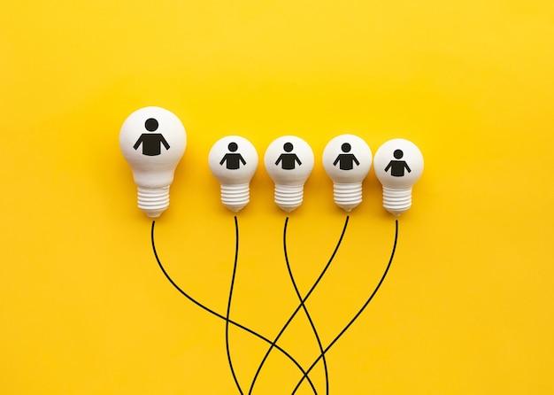 Conceptos de creatividad y liderazgo empresarial con bombilla sobre fondo amarillo