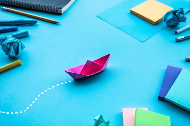 Conceptos de dirección o objetivo empresarial con papel de barco sobre fondo azul de la mesa de trabajo.ideas para el éxito de la inversión.reto de la situación