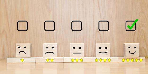Conceptos de evaluación de servicio al cliente y encuesta de satisfacción. la casilla de verificación seleccionada sonrisa de cara feliz y símbolo de cinco estrellas en el cubo de madera en la mesa