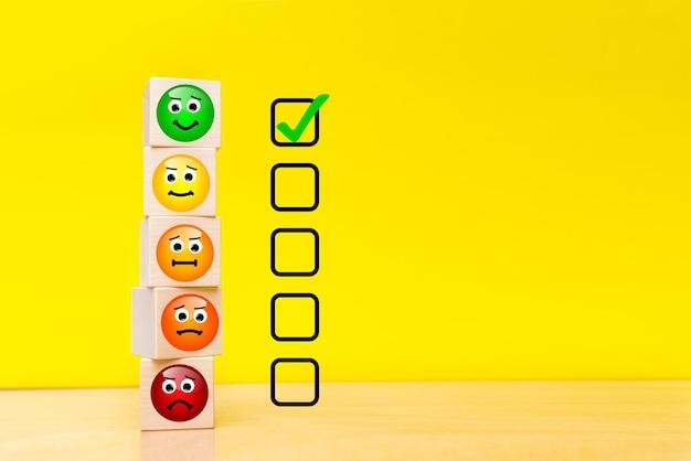 Conceptos de evaluación de servicio al cliente y encuesta de satisfacción. imágenes de emoticonos en cubos de madera. fondo amarillo con copia del espacio.