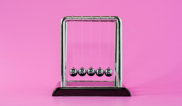 Conceptos de física de la cuna de newton para acción y reacción o causa y efecto sobre el fondo rosa