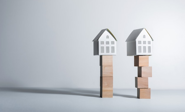 Conceptos inmobiliarios con casa modelo en caja de madera y plan de inversión empresarial.