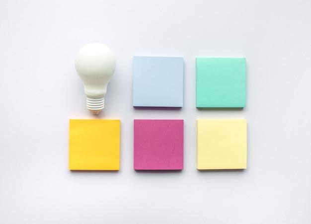 Conceptos de inspiración creativa con bombilla y papel de carta en colores