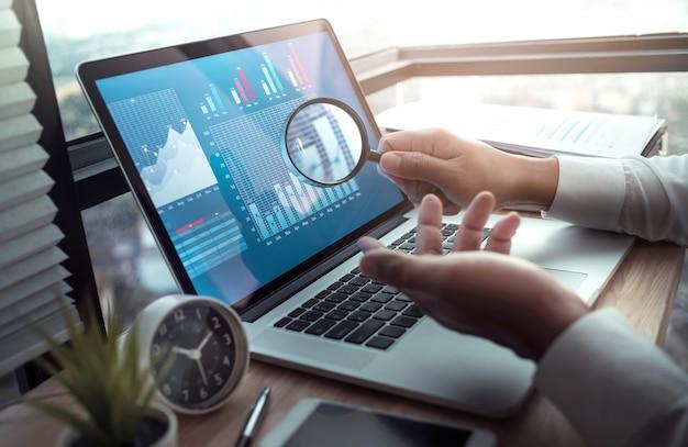Conceptos de negocio con empresario sosteniendo lupa con gráfico gráfico