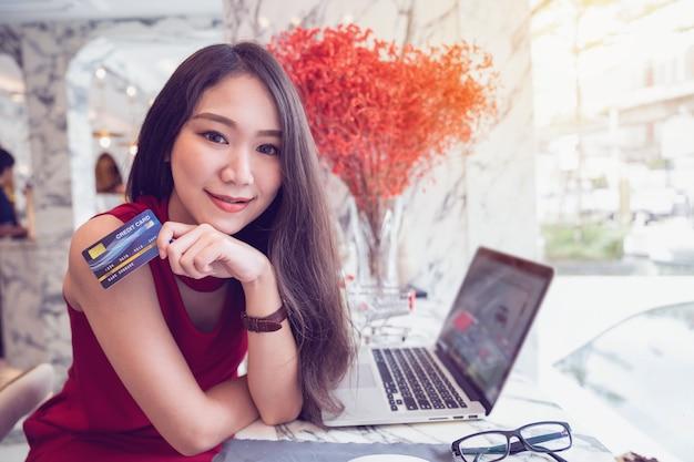 Conceptos de pago en línea, joven asiática sonriendo con tarjeta de crédito en las manos mientras compra en línea en la computadora portátil en la cafetería