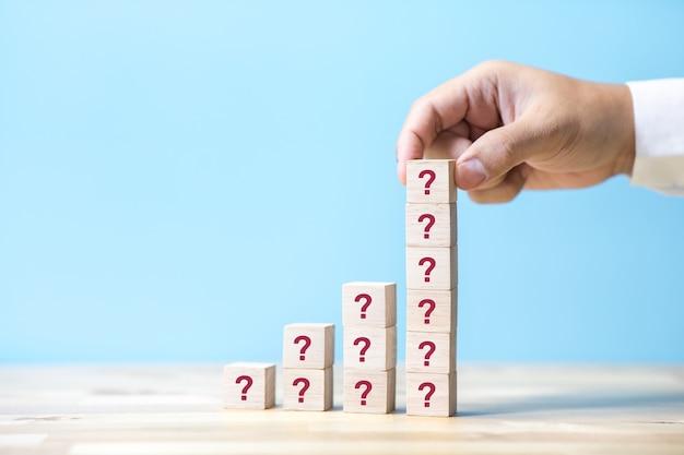 Conceptos de preguntas y respuestas con persona de negocios y firmar en caja de madera