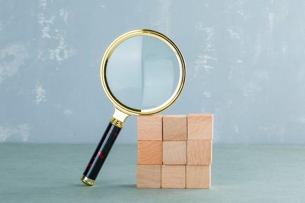 Conceptual de búsqueda con bloques de madera, vista lateral de la lupa.