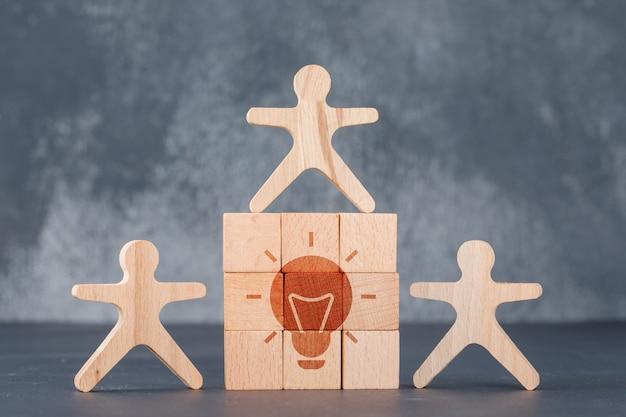 Conceptual de idea de negocio con pared de bloques de madera con icono de idea.