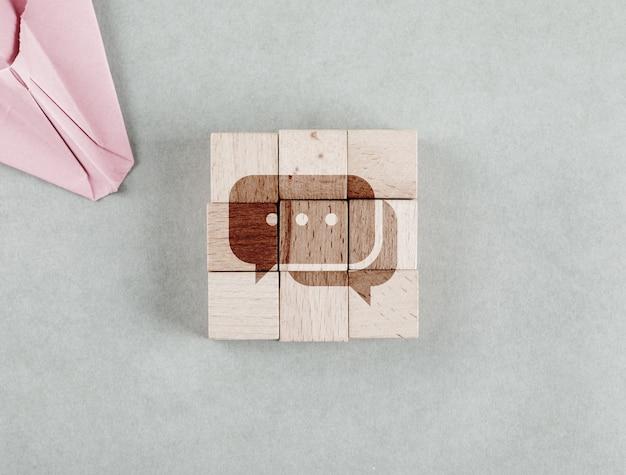 Conceptual de negocio con bloques de madera con vista superior del icono de mensaje bobble.