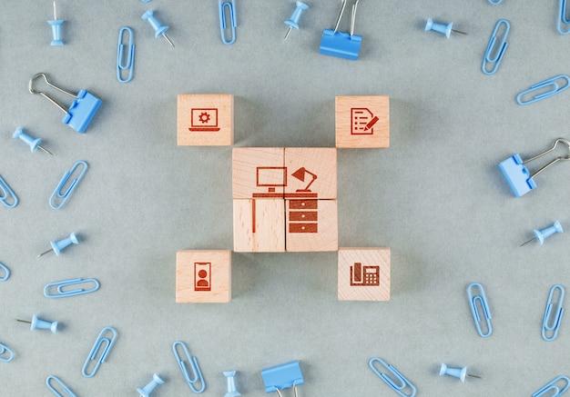 Conceptual de la oficina de negocios con bloques de madera con iconos, clips, clips de carpeta vista superior.
