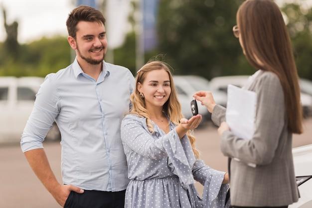 Concesionario de automóviles femenino que ofrece las llaves de una pareja