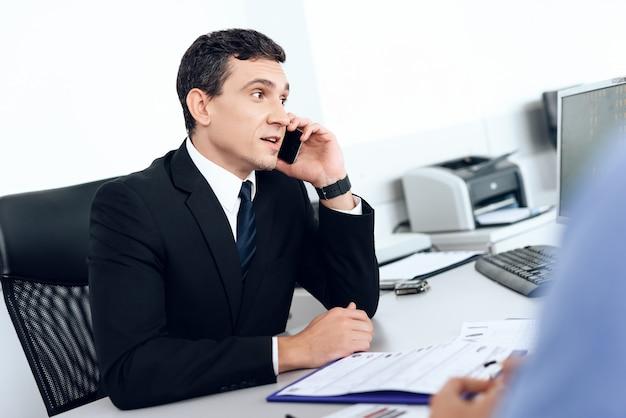 El concesionario de automóviles habla por teléfono en el concesionario de automóviles.