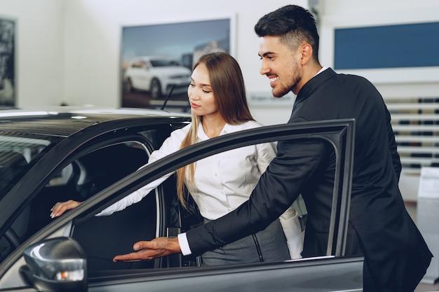 Concesionario de automóviles hombre mostrando a una mujer comprador un coche nuevo en el salón del automóvil