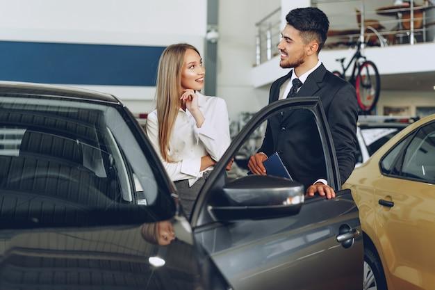 Concesionario de automóviles hombre mostrando a una mujer comprador un coche nuevo