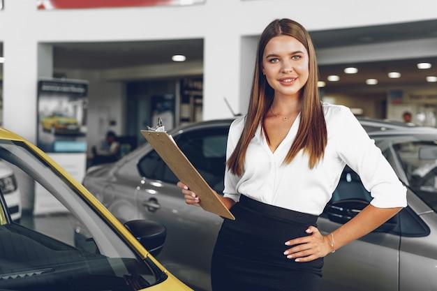 Concesionario de automóviles mujer joven atractiva de pie en la sala de exposición cerca de un coche nuevo