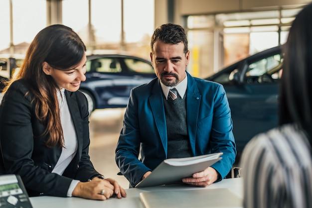 Concesionario de autos maduros mostrando contrato al cliente.