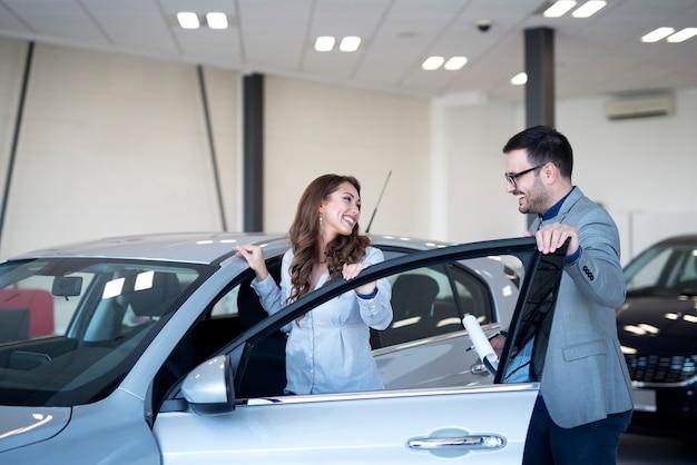 Concesionario de coches y cliente en la sala de exposición de vehículos eligiendo coche nuevo