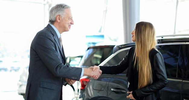 Concesionario de coches dando un apretón de manos a una mujer joven