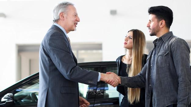 Concesionario de coches dando un apretón de manos a una pareja joven.
