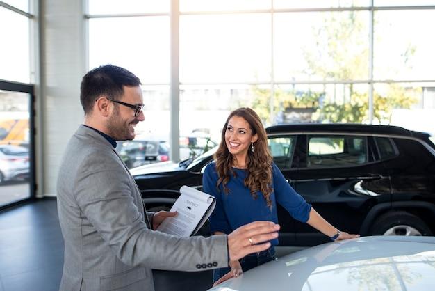 Concesionario de coches presentando coche nuevo al cliente