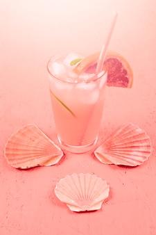 Concha de concha de peregrino cerca del cóctel frío de alcohol de toronja en vidrio empañado con menta y rodajas de pomelo sobre un fondo con textura de coral