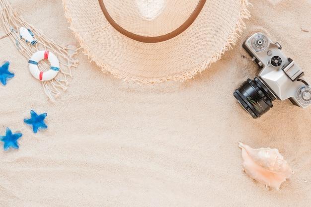 Concha de mar con sombrero de paja y cámara.