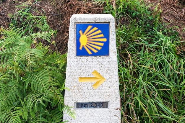 Concha de vieira amarilla, símbolo turístico del camino de santiago que muestra la dirección en el camino norte en españa.