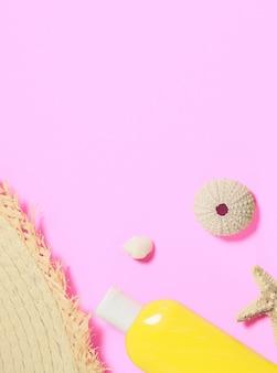 Conchas, una botella de loción de protección solar, un fragmento de un sombrero de paja sobre una superficie plana de color rosa