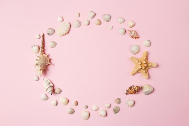 Conchas y estrellas de mar sobre un fondo rosa pálido.