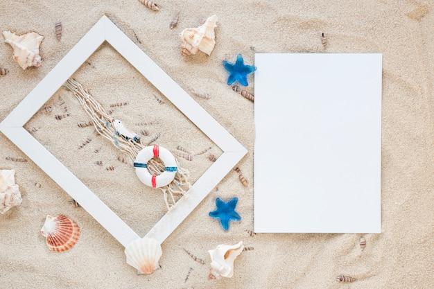 Conchas de mar con marco y papel en blanco sobre arena.
