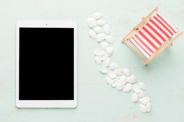 Conchas marinas y tableta en superficie ligera