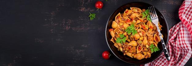Conchas de pasta italiana con champiñones, calabacín y salsa de tomate.