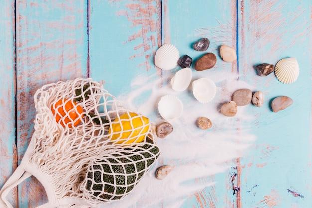 Conchas piedras arena y frutas en tablero de madera
