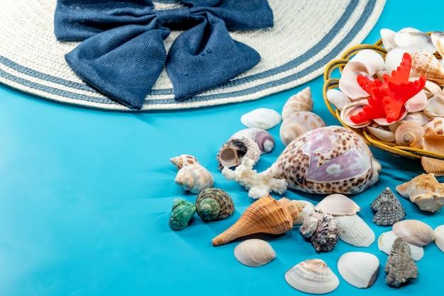 Conchas y sombrero de verano con rayas azules y lazo.