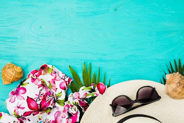 Conchas y traje de baño cerca de gafas de sol con sombrero.