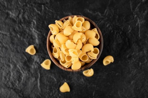 Conchiglie de pasta cruda italiana en cuenco de madera.