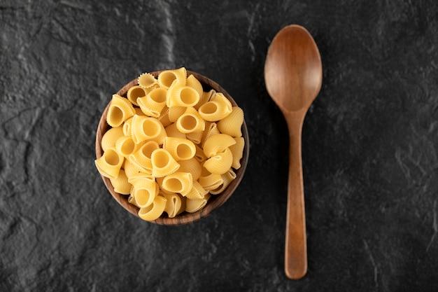 Conchiglie de pasta cruda italiana en recipiente de madera con una cuchara de madera.