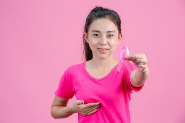 Concientización sobre el cáncer de mama, una mujer con una camisa rosa con una cinta rosa con la mano izquierda muestra el símbolo del día contra el cáncer de mama