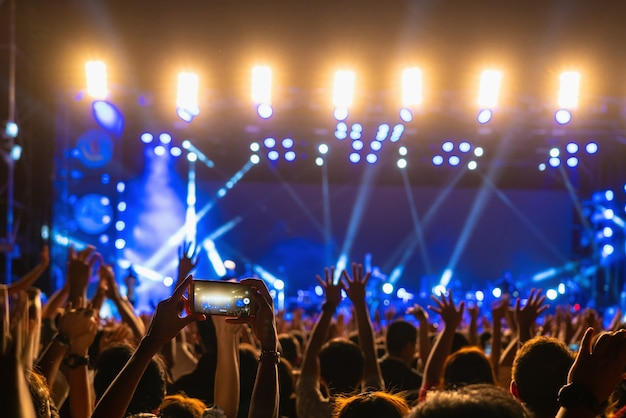 Concierto multitud de música fanclub mano usando teléfono celular tomando grabación de video o transmisión en vivo