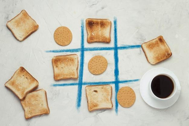 Concurso de elección de ceros y cruces juego de galletas y tostadas tostadas cuadradas, taza con café negro, fondo de piedra blanca vista plana, vista superior