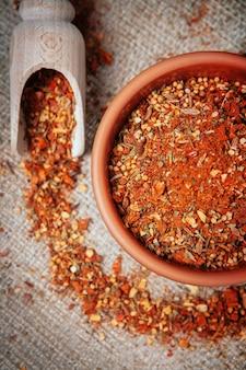 Condimento con trozos de laurel, hierbas, mostaza, pimienta y cúrcuma sobre arpillera