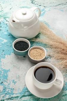 Condimentos de vista frontal y té en la superficie azul de la tetera de té