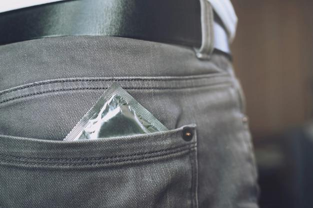Condón listo para usar en el bolsillo de los pantalones vaqueros, brinda un concepto de sexo seguro en la cama previene infecciones y los anticonceptivos controlan la tasa de natalidad o profiláctico seguro. día mundial del sida,