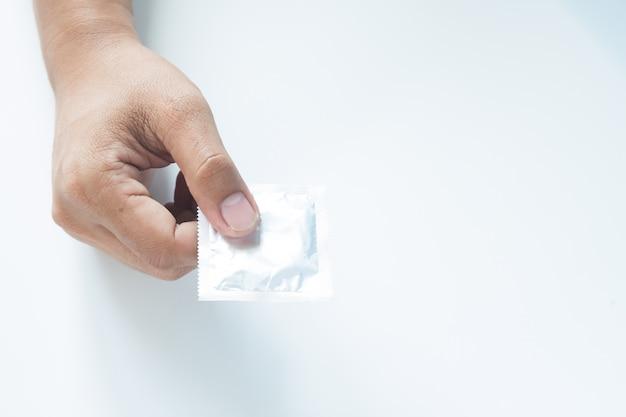 Condón en mano masculina sobre fondo blanco