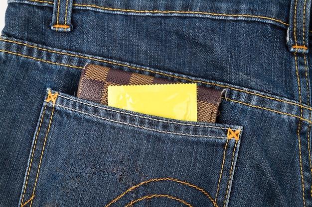 Condones y billetera en el bolsillo de los pantalones vaqueros