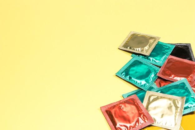 Condones coloridos de alto ángulo sobre fondo amarillo