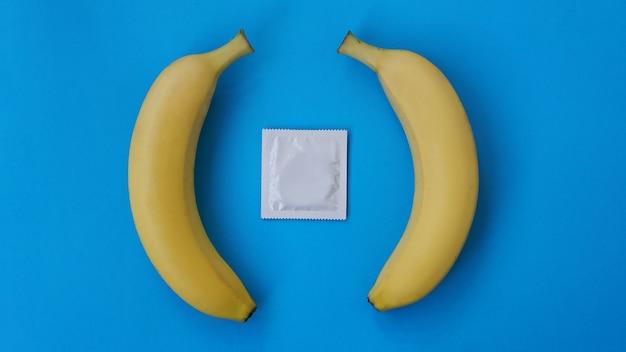 Condones y dos plátanos juntos sobre fondo azul, el concepto de anticonceptivos y la prevención de enfermedades venéreas del matrimonio entre personas del mismo sexo.
