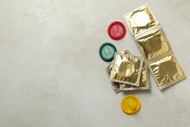 Condones multicolores en la pared con textura blanca, espacio para texto